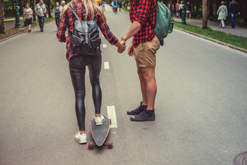 Blond female learnin ride longboard with casual male.