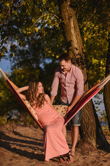 happy wife and husband in hammock on the beach