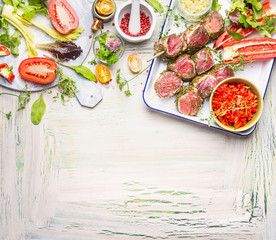 Meat skewers with fresh herbs, spices and vegetables ingredients for grill or cooking. Preparation on light wooden background, top view, border