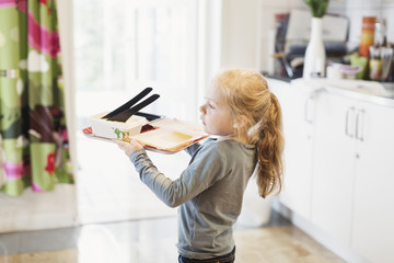 Girl carrying tray with food