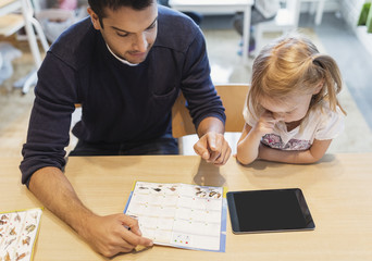 High angle view of teacher showing animal chart to girl in preschool