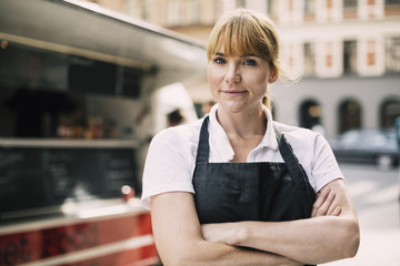 Portrait of confident chef with arms crossed standing in city