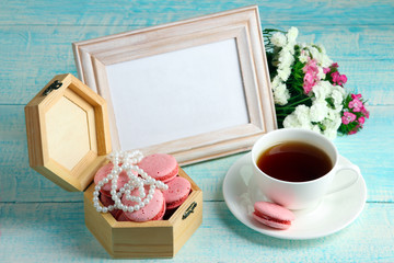 open wooden box on wooden background with macaroon and beads near to the Cup of strong coffee and flowers