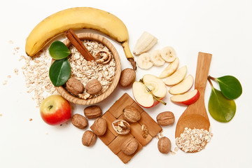 There are Banana,Apple,Orange with Walnuts in the Wooden Plate and Rolled Oats,Wooden Spoon,Trivet,with Green Leaves,Healthy Fresh Organic Food on the White Background