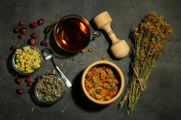 dried flowers of herbs with tea and a wooden spoon with a glass of bowl on wooden background