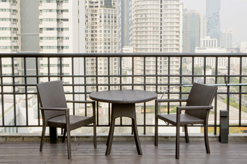 Empty tables and chairs at terrace with high building view