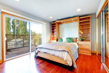 Bright bedroom with storage combination, hardwood floor and glas