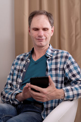 Mature man with tablet at home