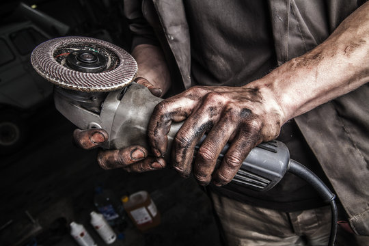 Dirty hands with angle grinder