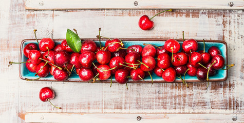 Blue bowl with sweet cherry harvest  on light wooden background, top view