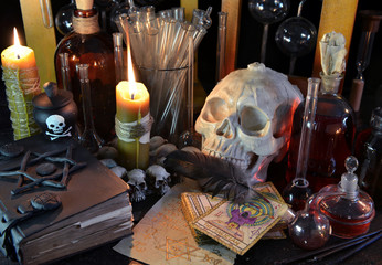 Still life with skull, tarot cards, candles and magic bottles