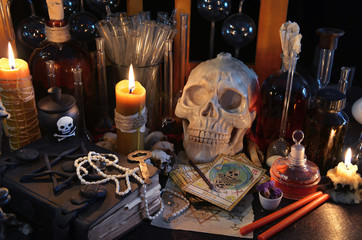 Magic still life with tarot cards, skull, book and burning candles