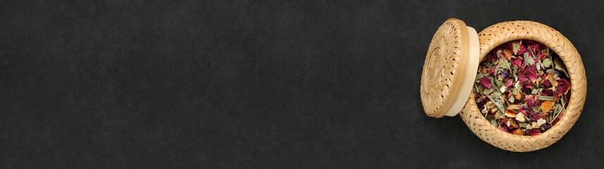 Tisane de pétales de fleurs dans une boîte en osier sur ardoise, carte, menu, bannière