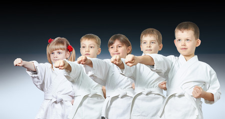 Five little athletes hit a punch on a gradient background