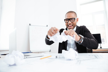 Angry businessman tearing up a document in office