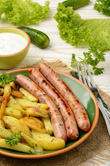 Grilled white sausages with roasted potatoes.