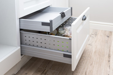 Fototapeta Kitchen cupboard with opened drawer and inner drawer inside obraz