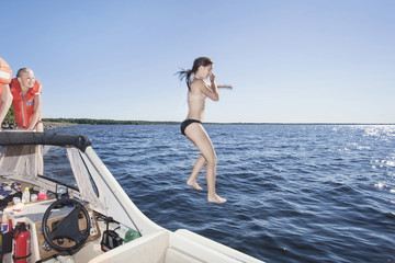 Side view of young woman jumping in sea against clear sky