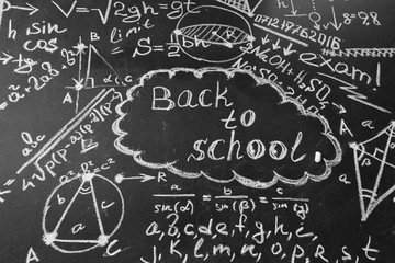 "Back to school background with title ""Back to school"" and formulas written by white chalk on the chalkboard"