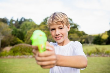 Kid posing at camera during a sunny day with his water gun