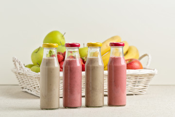 Fruit basket and strawberry and banana smoothie in a glass bottl