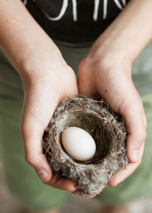 Child holding a nest in his hands. Inside is an egg
