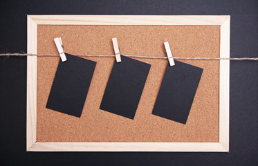 black cards hanged on a nylon thread. corkboard background.