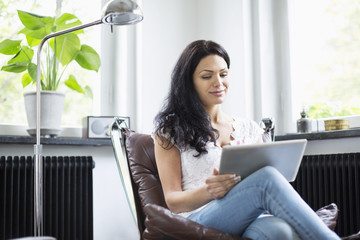 Mid adult woman using digital tablet at home