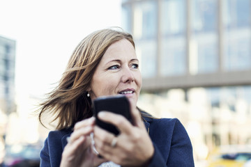 Businesswoman looking away while using mobile phone outdoors