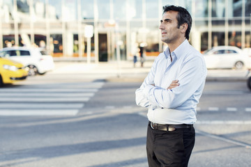 Businessman with arms crossed looking away while standing by city street