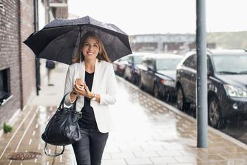 Portrait of smiling businesswoman walking on sidewalk with umbrella during rainy season