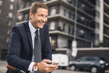 Happy businessman using smart phone in city