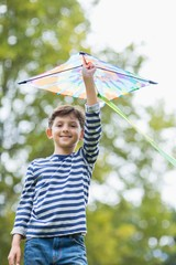Boy holding a kite in park