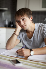 Bored man looking away while studying at table in house
