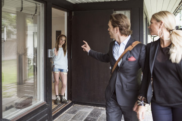 Parents instructing daughter while leaving home