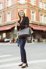 Full length of smiling businesswoman looking away while using mobile phone on city street