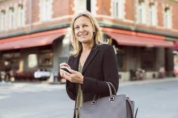 Happy businesswoman looking away while using mobile phone on city street