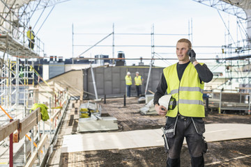 Young man talking on mobile phone at construction site