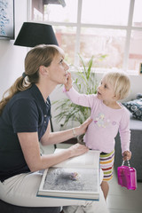 Girl putting make-up on mother at home
