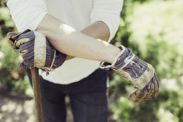 Midsection of man wearing gardening gloves at yard
