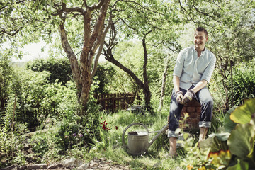 Happy young man relaxing while gardening at yard