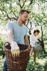 Man carrying wicker basket with woman gardening in background at yard