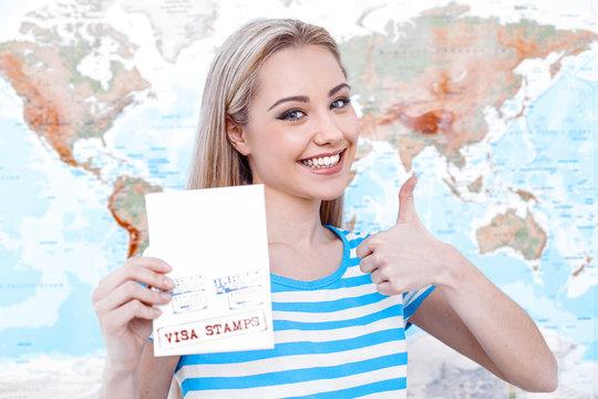Beautiful young woman near map