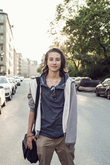 Portrait confident male high school student standing on city street