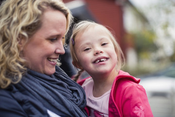 Portrait of happy girl with down syndrome carried by mother