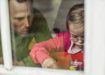 View of father and daughter looking down through window