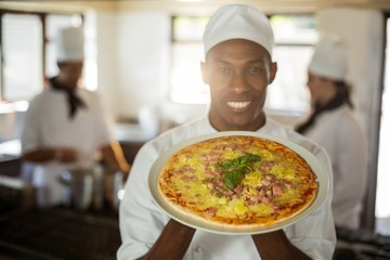 Portrait of smiling chef showing pizza  Wall mural