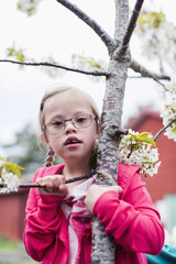 Portrait of girl with down syndrome holding tree branch in yard