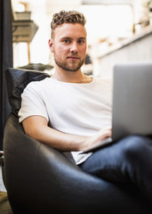 Portrait of confident young businessman using laptop while sitting on bean bag chair in new office