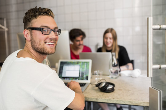 Portrait of happy young businessman with colleagues in background at creative office